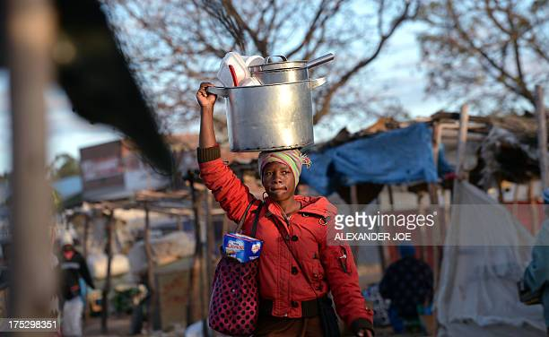 A female vendor cooking food is on her way in Jambanja market in Seke 58km south of Harare on August 2 2013 Zimbabwe President Robert Mugabe's party...
