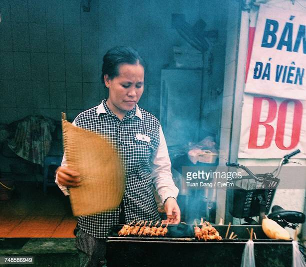 Female Vendor Selling Barbecue Meat On Street
