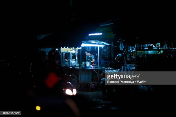 female vendor standing at concession stand during night - one night stand stock-fotos und bilder