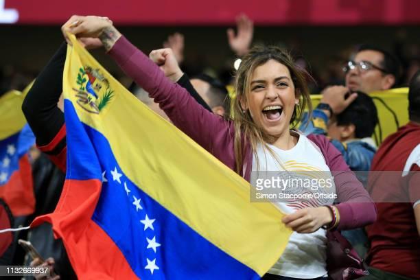 A female Venezuela fan celebrates with her flag during the international friendly match between Argentina and Venezuela at Estadio Wanda...