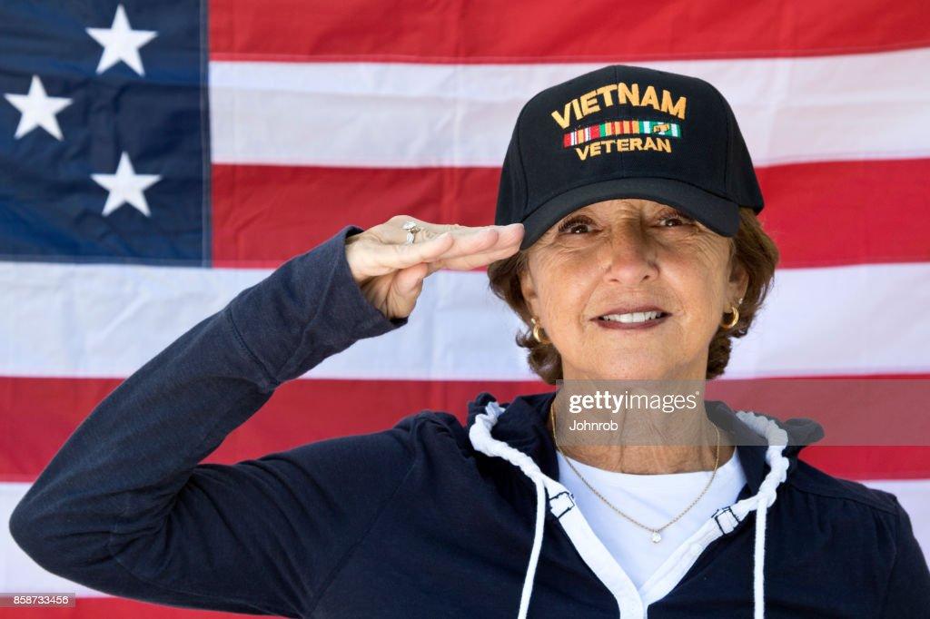 Feminino Vietnam veterano saudando procurando conteúdo vestindo boné veteranos, com a bandeira americana no fundo. : Foto de stock
