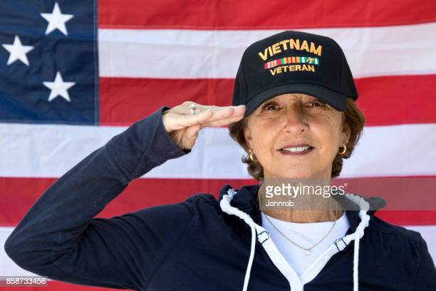 female vietnam veteran saluting  looking content wearing veterans cap, with american flag in background. - veterans day background stock photos and pictures