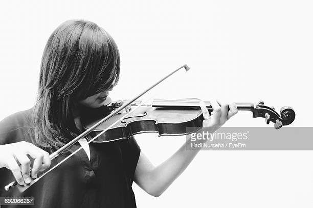Female Violinist Playing Violin Against White Background