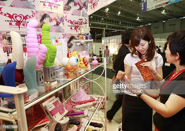 A female visitor admires an adult toy at a sex toy shop for women Love Peace Club at the Adult Treasure Expo in Makuhari Chiba prefecture 27 July...