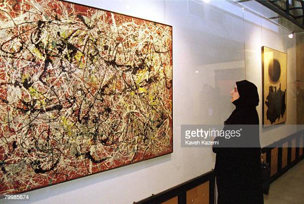 A female visitor fully covered in a black chador views 'Mural On Indian Red Ground' by American abstract expressionist painter Jackson Pollock at the...