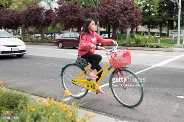 Female visitor to Google Inc rides a colorful Google Bike at the Googleplex, headquarters of Google Inc in the Silicon Valley town of Mountain View,...