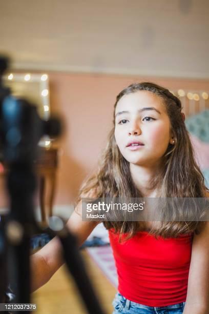 female vlogger adjusting camera while sitting in bedroom - ein mädchen allein stock-fotos und bilder