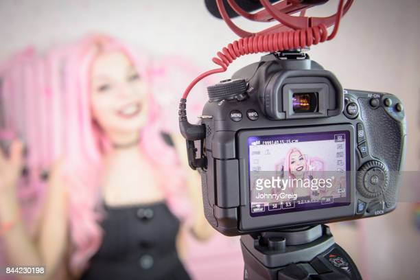 female vlogger on video camera making film for social media - influencer photos stock photos and pictures