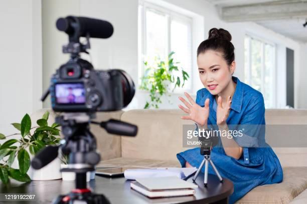 weibliche vloggerin, die einen videoblog aufnimmt - izusek stock-fotos und bilder