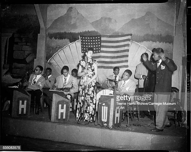 Female vocalist performing on stage with band including Walt Harper conducting Bradley Bluett on saxophone on left Harry Nash on trumpet back left...