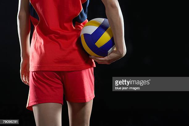 a female volleyball player holding a volleyball. - volleyball sport stock pictures, royalty-free photos & images