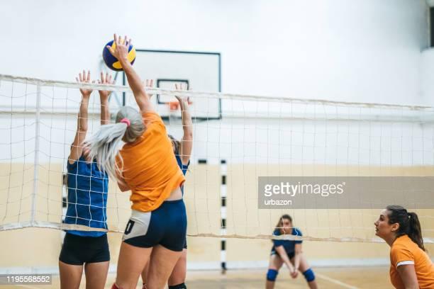 volleyballerin spuckt den ball - volleyball mannschaftssport stock-fotos und bilder