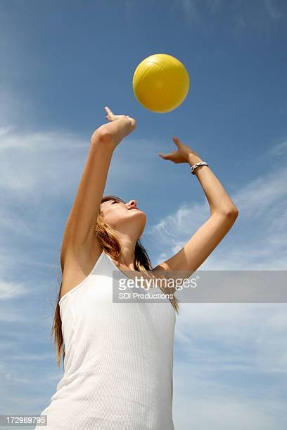 female volleyball player throws yellow ball into the blue sky - hot body girls stock photos and pictures