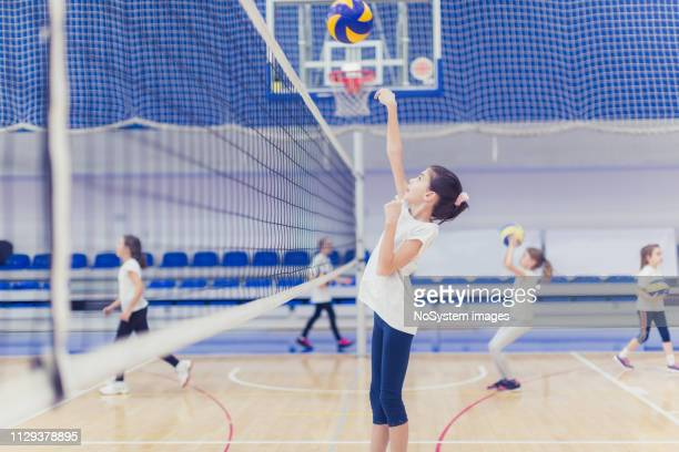 female volleyball team exercising indoors - drive ball sports stock pictures, royalty-free photos & images