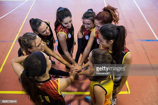 female volleyball team huddling and stacking hands - volleyball sport stock pictures, royalty-free photos & images