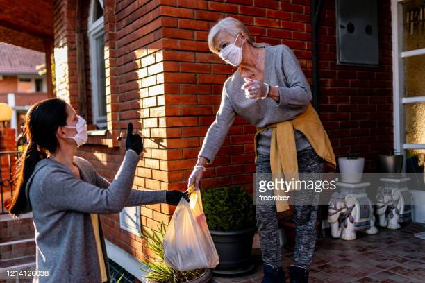 female volunteer bringing groceries to a senior woman at home - face mask protective workwear stock pictures, royalty-free photos & images