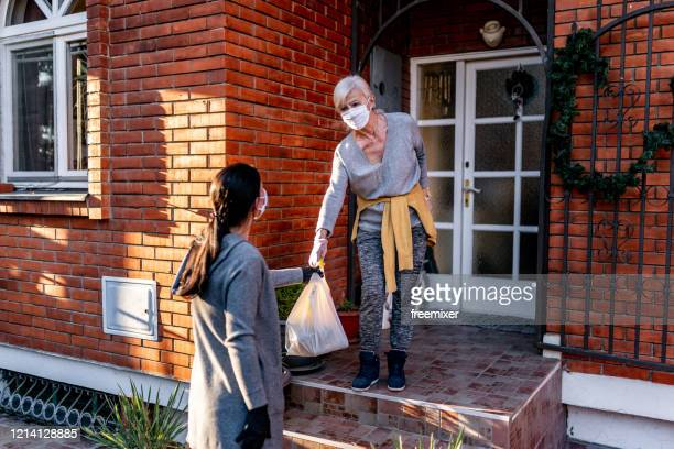 female volunteer bringing groceries to a senior woman at home - helping hand stock pictures, royalty-free photos & images