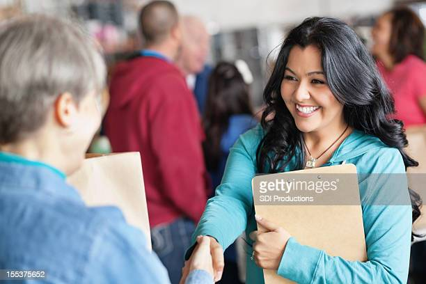 female volunteer greeting woman at donation facility - non profit organization stock pictures, royalty-free photos & images
