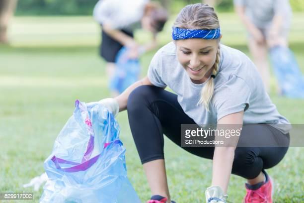 Female volunteer picks up trash in park