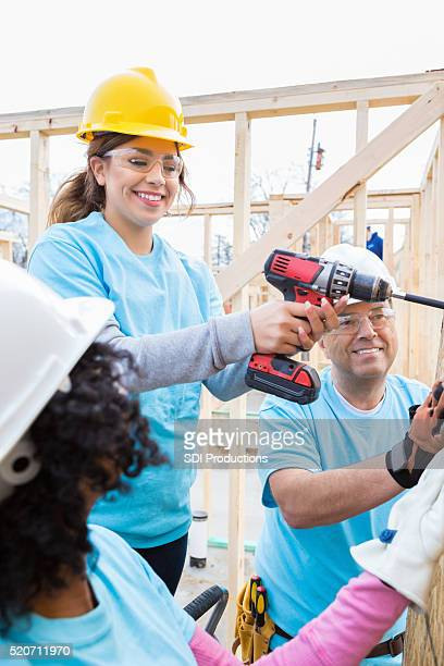 Female volunteer uses power drill at construction site