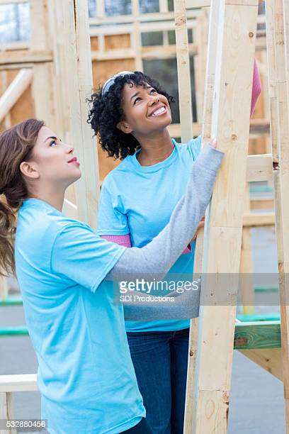 female volunteers at charity home construction site - community building stock pictures, royalty-free photos & images