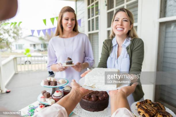 Female volunteers serve cake during charity event