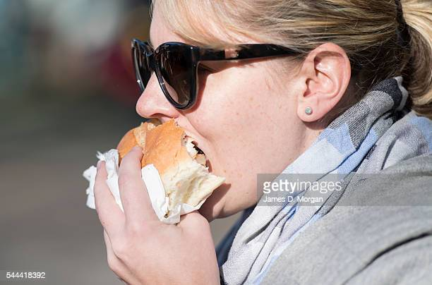 A female voter in the voting queue with her sausage sizzle on July 2 2016 in Sydney Australia Sausage sizzles have over time become an Australian...