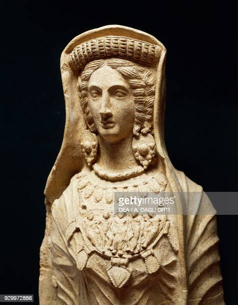 Female votive figurine in terracotta with an updo hairstyle veil large earrings breast plate bearing human likenesses in relief 4th century BC Italic...