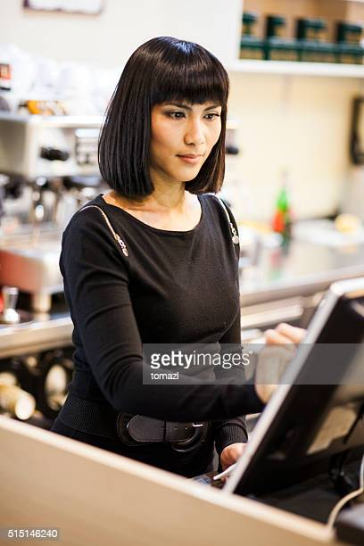 Female waiter entering order in computer