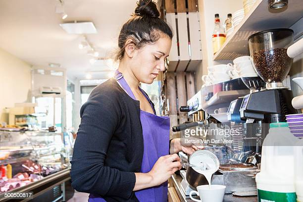 female waitress making coffee in delicatessen shop