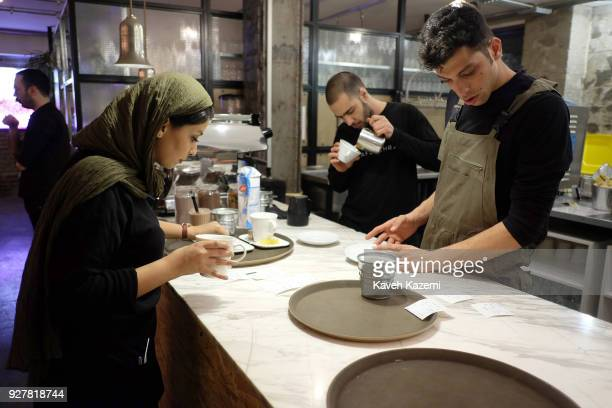 A female waitress prepares a hot drink while a waiter in the background makes a Cappuccino coffee in V Café on March 3 2017 in Tehran Iran V Café is...