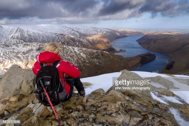 female walker sits at the top of harter fell overlooking haweswater. lake district national park. uk. - loughrigg fells - fotografias e filmes do acervo