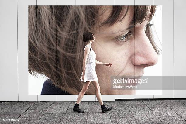 A female walking in front of her own poster