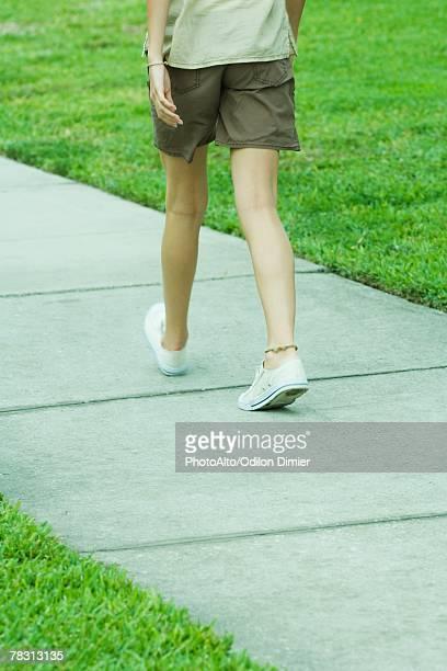 Female walking on sidewalk, waist down, rear view