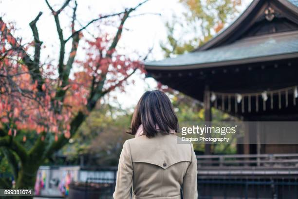 female walks on the grounds of a shrine