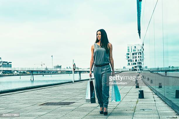 Female walks with shopping bags outside