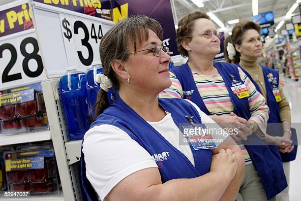 Female WalMart employees look on as a manager rewards an employee with a plaque a common practice in the company on March 16 2005 in Bentonville...