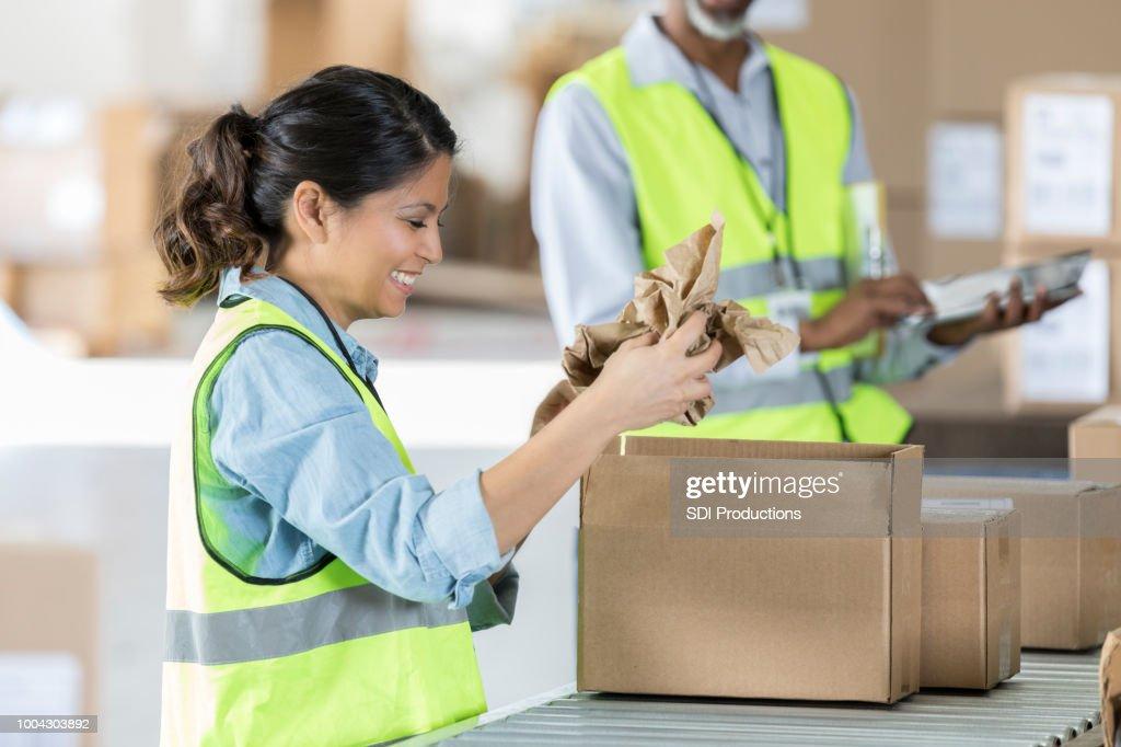 Empregado de armazém feminino prepara pacote para entrega : Foto de stock