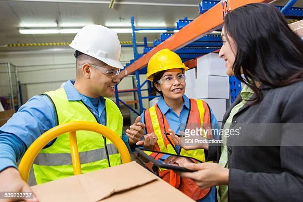 Superviseur d'entrepôt femme parlant avec col bleu travailleurs