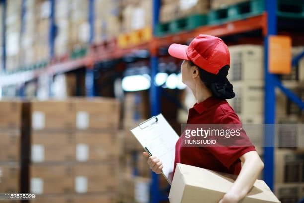 Female warehouse worker holding cardboard box in logistics warehouse