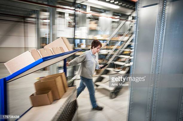 Female warehouse worker moving trolley cart