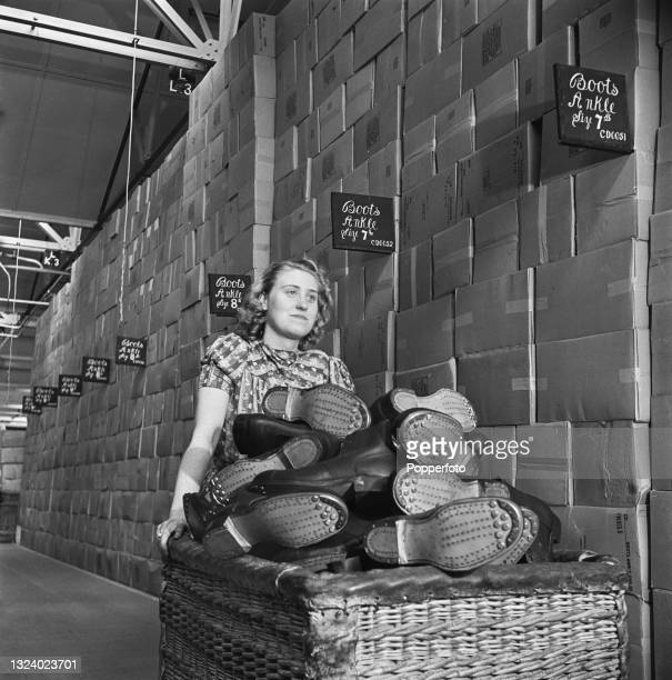 Female warehouse worker pushes a wicker basket full of Britsh Army standard issue Ammunition boots past stacks of hobnail boot boxes at a Central...