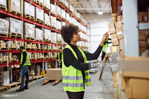 Female warehouse worker stacking boxes onto the rack