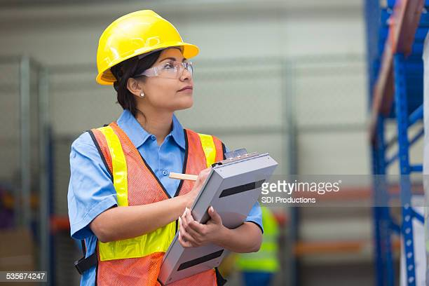 Female warehouse worker taking inventory with clipboard