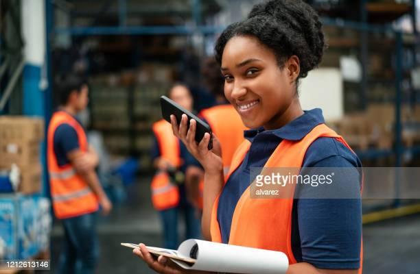 vrouwelijke pakhuisarbeider die op telefoon spreekt - directrice stockfoto's en -beelden