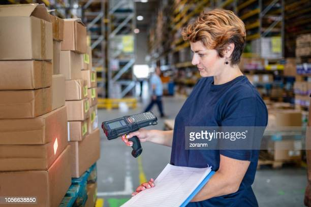 Female warehouse worker using bar code reader beam