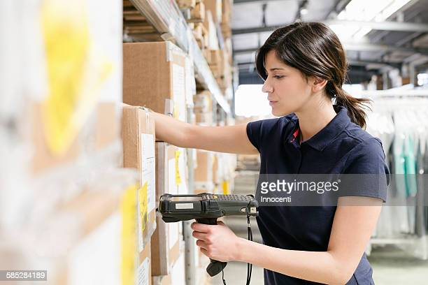 Female warehouse worker using barcode scanner on box in distribution warehouse