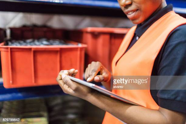 Trabajador de almacén femenino con tableta digital
