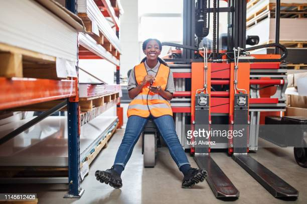 female warehouse worker with a mobile phone - transportation occupation stock pictures, royalty-free photos & images