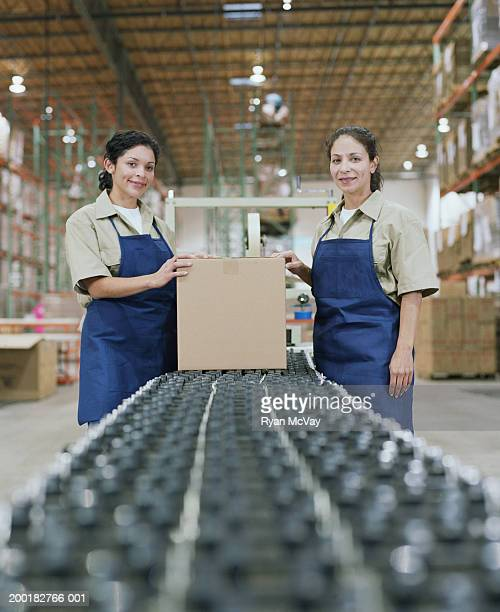 Female warehouse workers at assembly line, portrait